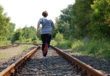 Mann rennt sehr schnell auf Bahngleisen.