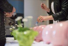 Geldschein wird in Sparschwein gesteckt.