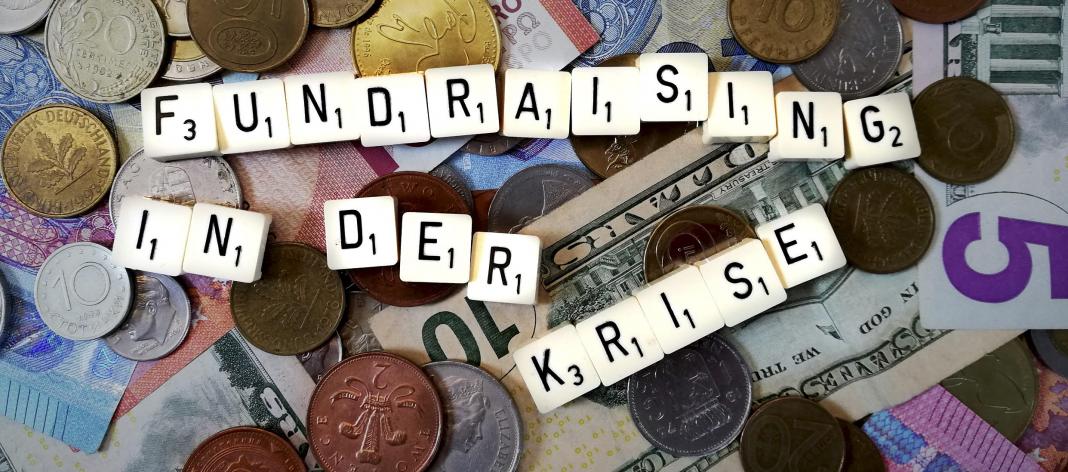 Fundraising in der Krise - dargestellt mit Scrabble-Steinen auf Geldscheinen und Münzen